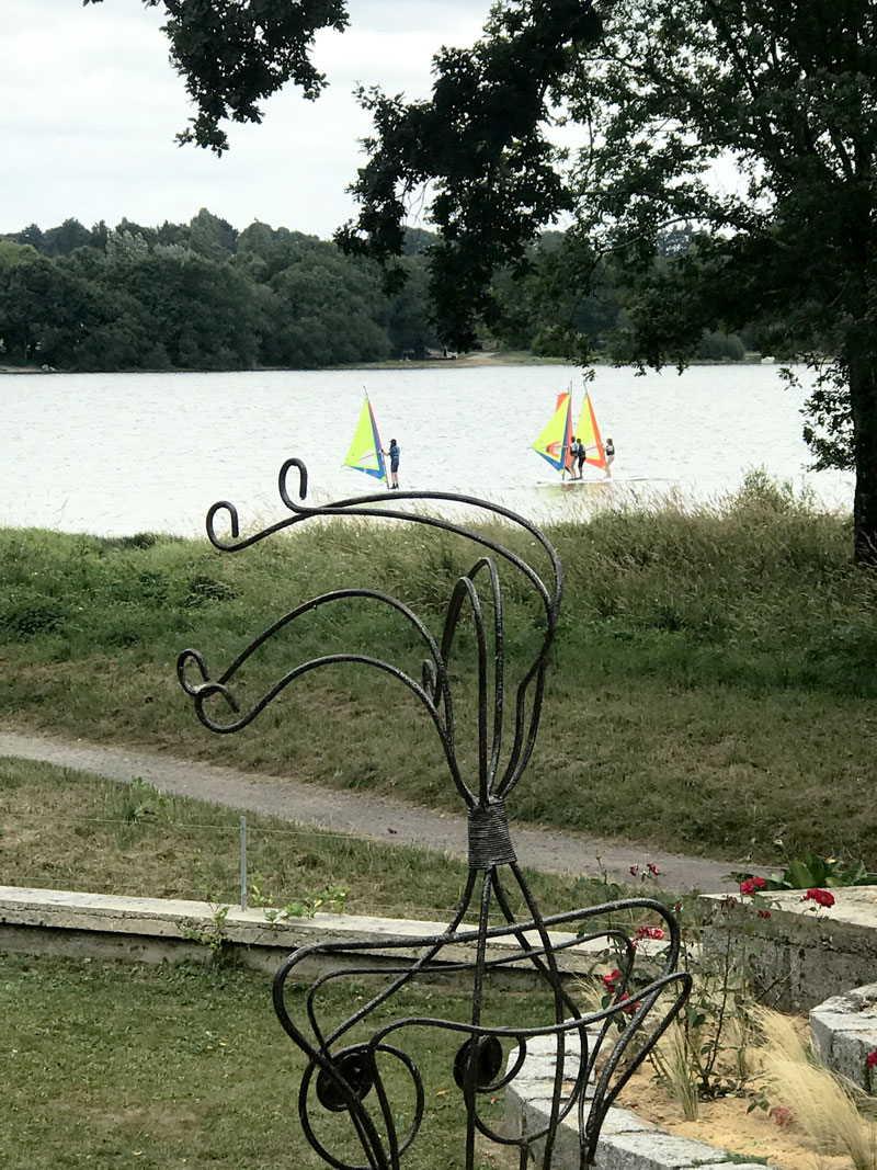 Une statue devant le Lac au Duc avec 3 planchistes